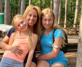 mom hugs two daughters at camp